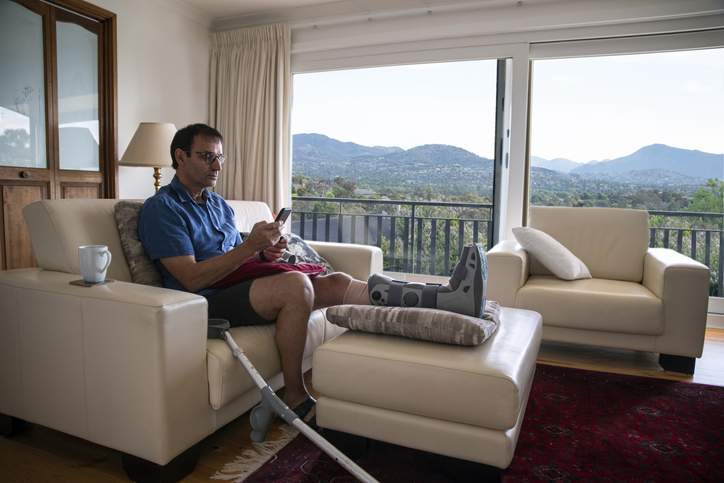 Man with broken leg rehabilitating at home