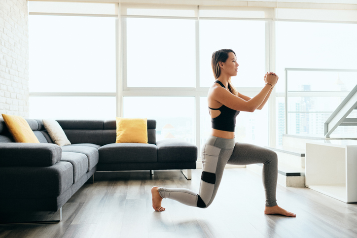 Female working out at home with lunges exercise