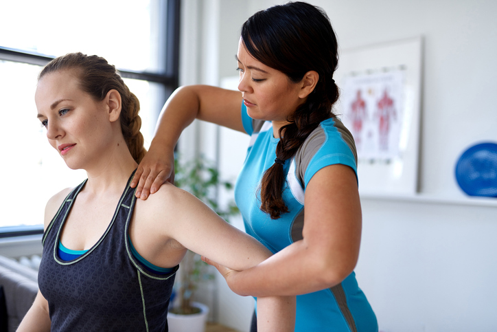 Physiotherapist mobilising shoulder joint of a female patient to treat shoulder pain