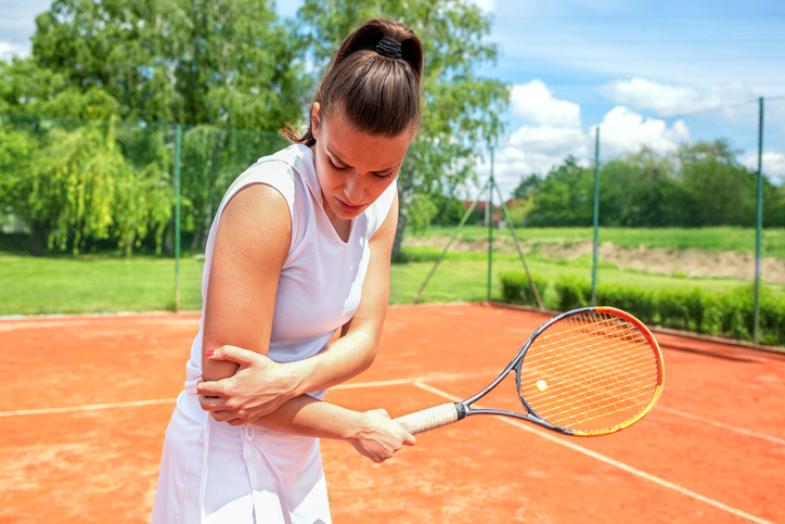Female playing tennis with elbow pain / tennis elbow