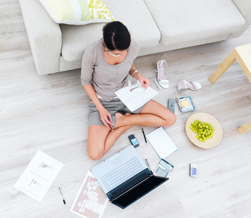 Female working cross-legs on the floor with laptop with poor posture