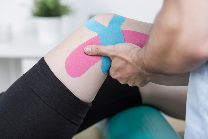 Male patient having kinesiotape taping therapy for knee pain