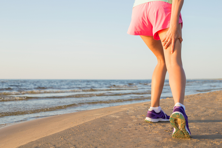 Running girl injured hamstring on beach