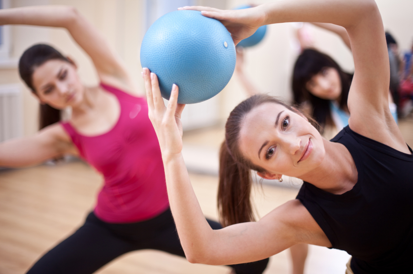 Group of people doing pilates with exercise ball