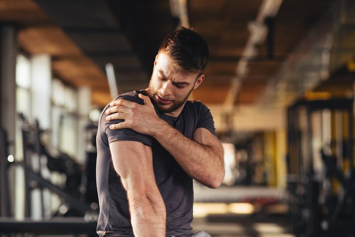 Male athlete with shoulder pain in gym