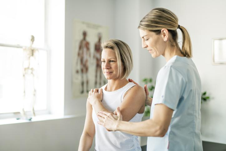 Physiotherapist applying muscle energy technique on female patient's elbow