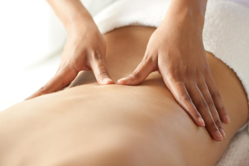 Patient with back pain receiving sports massage and physiotherapy